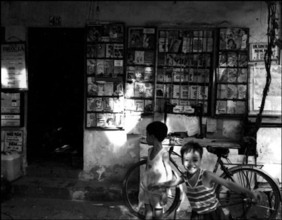 Những đứa trẻ chơi đùa trước một hiệu sách cũ ở Hà Nội.