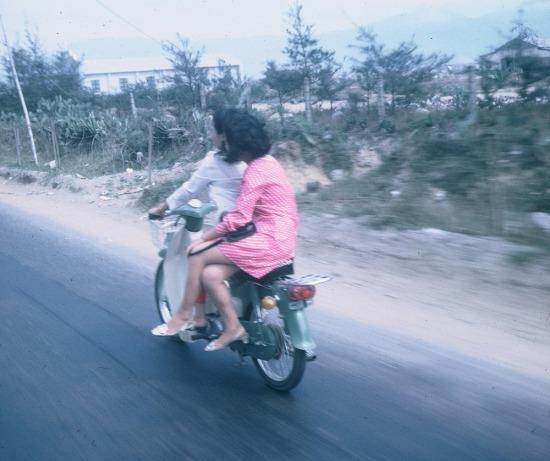 Một cặp đôi chở nhau trên đường bằng xe Honda Cub.