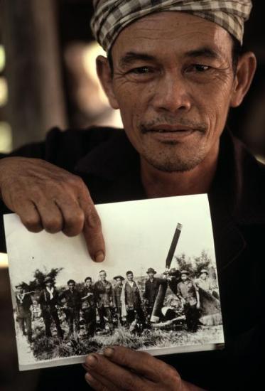 Ông Võ Văn Chấp, một cựu binh 56 tuổi của Mặt trận Dân tộc Giải phóng, giữ bức ảnh của mình và các đồng đội bên xác một chiếc máy bay trực thăng Mỹ bị đơn vị của ông bắn hạ gần Củ Chi ngày 19/4/1971.
