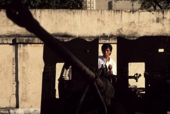 Một thanh niên ngồi trên khẩu pháo lính Mỹ từng sử dụng trong chiến tranh Việt Nam.