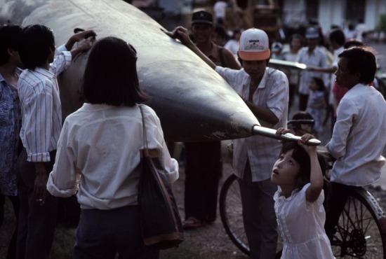 Một bé gái sinh sau năm 1975 đu mình trên mũi của một chiếc máy bay Mỹ từng tham chiến trên bầu trời Việt Nam.