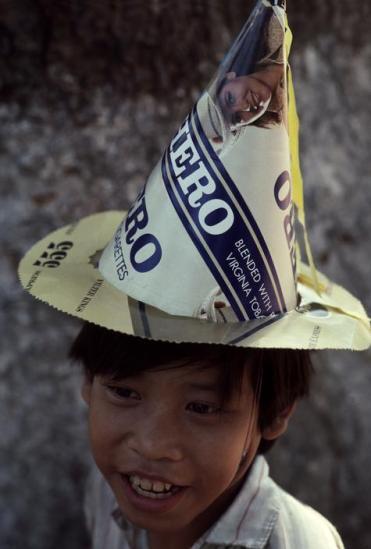 Một cậu bé đội chiếc mũ được làm từ vỏ hộp thuốc lá ngoại. Đây là mốt mới của trẻ em TP. HCM dịp Tết 1988.