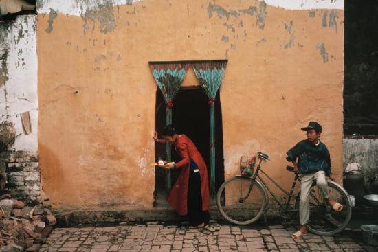 Một người phụ nữ mặc trang phục truyền thống, trên tay cầm đĩa hoa quả cúng.
