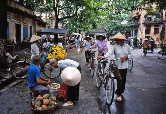 Những người phụ nữ dắt xe đạp đi chợ.