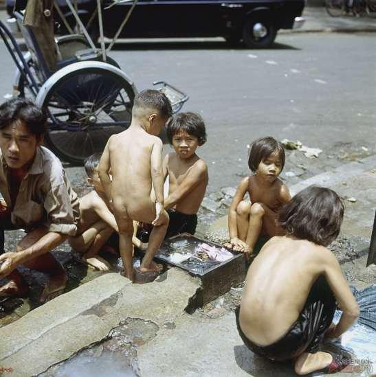 Trẻ em tắm giặt ngay trên vỉa hè.