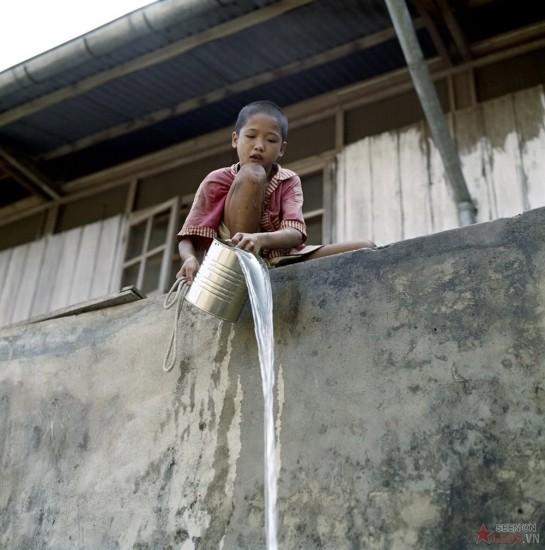 Cậu bé múc nước bằng xô thiếc.