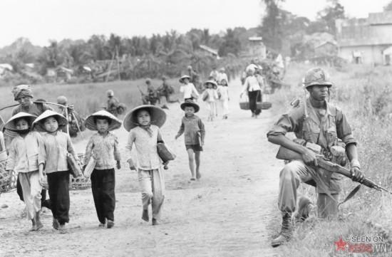 Phụ nữ và trẻ em Việt Nam trên đường từ trường học trở về nhà ở làng Xuân Điền, Bến Cát, Việt Nam. Các binh sĩ thuộc sư đoàn bộ binh số 1 cảnh giới nghiêm ngặt trên con đường này.