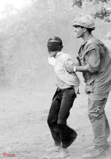 Lính Mỹ áp giải một người tình nghi là Việt Cộng giữa đám bụi mịt mù được tạo ra bởi cánh quạt trực thăng, ngày 18/4/1966.