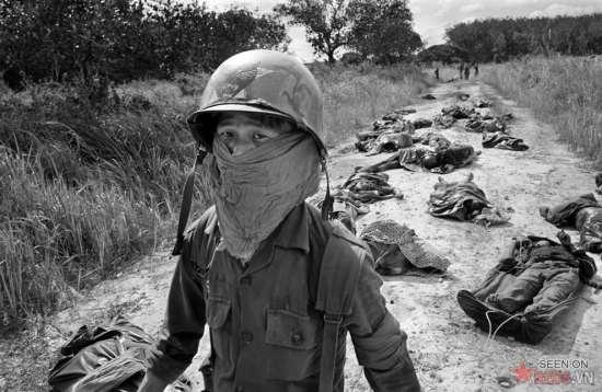 Một người lính VNCH phải bịt mặt để tránh mùi tử khí khi vượt qua một con đường đầy xác lính Mỹ và Việt Nam sau cuộc đụng độ với quân du kích ở đồn điền cao su Michelin, khoảng 45 dặm về phía Đông Bắc Sài Gòn, ngày 27/11/1965. Hơn 100 thi thể đã được thu hồi sau trận đánh.