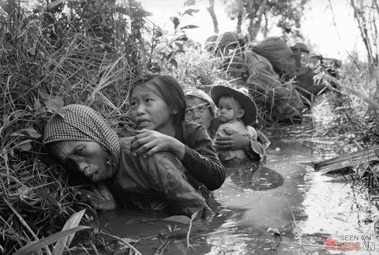 Phụ nữ và trẻ em cúi mình trong một con kênh bùn để tránh đạn trong một cuộc giao tranh tại một vị trí cách phía Tây Sài Gòn khoảng 20 dặm, ngày 1/1/1966.