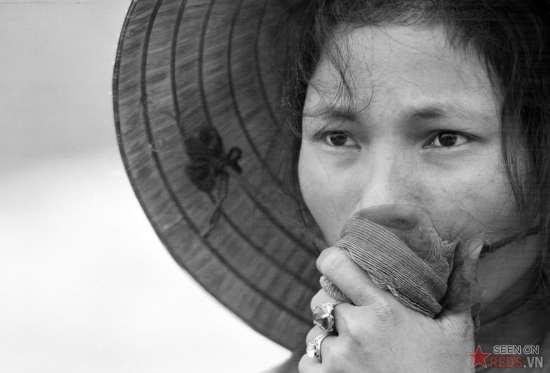 Một phụ nữ đang nhìn ngôi mộ tập thể được khai quật tại Điện Bài, phía Đông của Huế vào tháng 04/1969. Cô lo sợ rằng chồng, cha và em trai của cô – những người mất tích từ dịp tết Mậu Thân - đã bị chết.