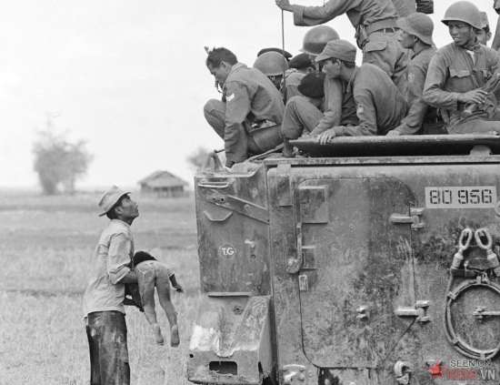 Một người cha ôm xác con trong khi toán lính biệt kích của quân đội VNCH nhìn xuống từ xe thiết giáp, ngày 19/3/1964. Đứa trẻ đã bị chết khi lực lượng VNCH truy đuổi quân du kích trong một ngôi làng gần biên giới Campuchia. Đây là tấm ảnh đoạt giải Pulitzer năm 1965 của Horst Faas.