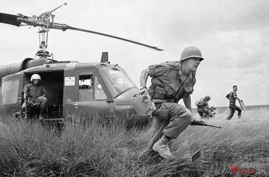 Một người lính VNCH cầm súng lục đã lên đạn khi tra vấn hai du kích nghi là Việt cộng bị bắt trong một đầm lầy đầy cỏ dại ở vùng đồng bằng phía Nam cuối tháng 8/1962. Người bị bắt bị lục soát, trói chặt và thẩm vấn trước khi bị dẫn đi cùng với những người tình nghi khác.