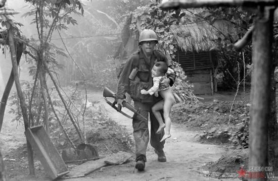 Một lính Mỹ thuộc đại đội A, tiểu đoàn 1, sư đoàn bộ binh số 16 mang một đứa trẻ đang khóc từ làng Cam Xe sau khi ném một lựu đạn phốt pho vào một công sự trong chiến dịch gần khu trồng cao su Michelin, Tây Bắc Sài Gòn, ngày 22 /8/1966. Một trung đội của Sư đoàn bộ binh số 1 đã bố ráp ngôi làng, lùng sục những tay súng bắn tỉa đã gây ra nhiều thương vong. Binh lính đã xua khoảng 40 cư dân ra khỏi ngôi làng trước khi pháo kích phá huỷ hoàn toàn ngôi làng.