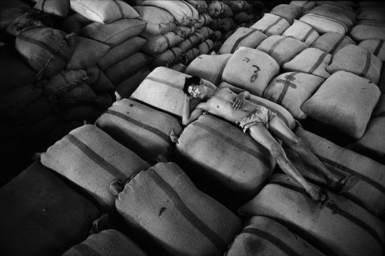 Một người công nhân nằm nghỉ trên các bao tại gạo tại một nhà kho ở TP HCM. Khoán 10 được thực hiện từ năm 1988 đã cởi trói cho nền nông nghiệp, biến Việt Nam từ một nước thiếu lương thực thành nước xuất khẩu gạo lớn kể từ năm 1989.