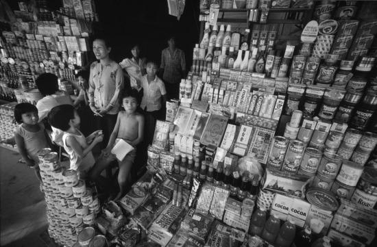 """Thực phẩm ngoại được nhập khẩu và xuất hiện ngày càng nhiều tại các cửa hàng. Trước đó phần lớn những mặt hàng kiểu này được đưa vào Việt Nam dưới dạng """"bưu kiện thực phẩm"""" gửi người thân, từ đó phân phối tới các quầy hàng vỉa hè."""
