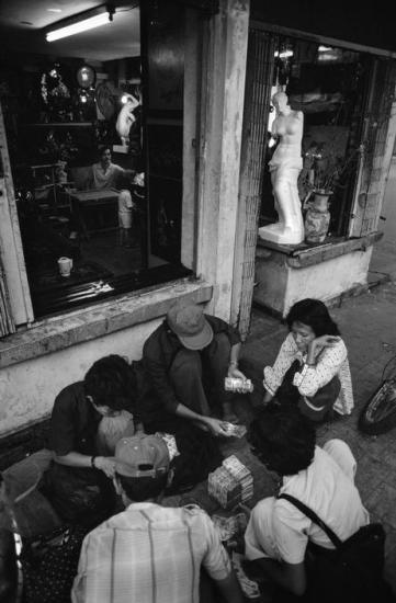 Một nhóm người buôn bán đang đếm đống tiền lẻ của mình. Tốc độ lạm phát ở Việt Nam đã tăng rất nhanh trong giai đoạn Đổi Mới.