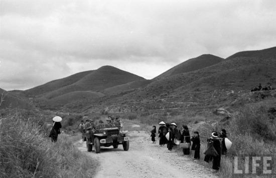 Người dân địa phương tò mò đứng nhìn khi một chiếc xe chở lính Pháp chạy qua