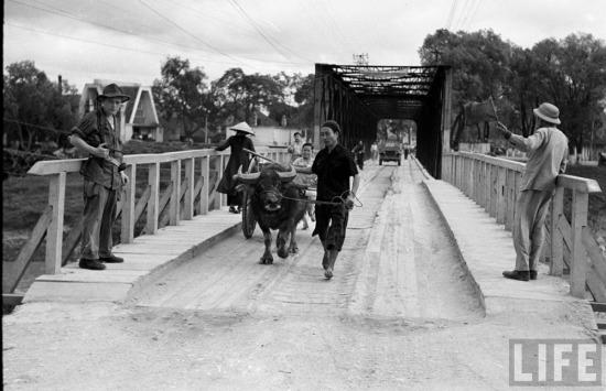 Người dân và binh lính qua lại trên cầu.