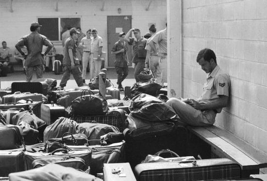 Một phi công với rất nhiều hành lý bao quanh đang đọc tiểu thuyết trong lúc chờ làm thủ tục ở trại Alpha trên sân bay Sài Gòn Tân Sơn Nhất. Bức ảnh chụp ngày 27/3/1973, khi hơn 900 phi công cùng tất cả lính Mỹ sắp rời khỏi Việt Nam.
