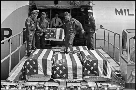 Quan tài của lính Mỹ thiệt mạng trong một vụ nổ ở đường băng sân bay được đưa xuống căn cứ không quân Travis, ở California ngày 28/5/1965.