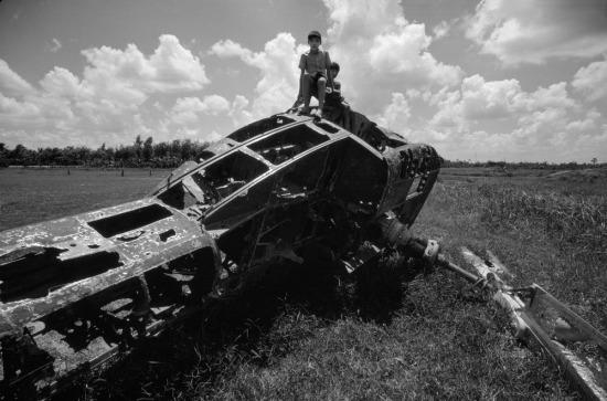 Hai cậu bé ngồi trên xác trực thăng Mỹ để lại từ thời chiến.