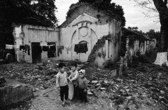 Trẻ em bên một khu nhà bị đạn bom phá hủy ở nông thôn Việt Nam.
