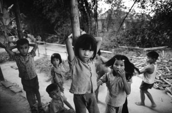 Trong một ngôi làng từng bị hủy diệt, những đứa trẻ của một số gia đình còn sống sót sau cuộc chiến đang chờ đợi những ngôi nhà được xây dựng lại.