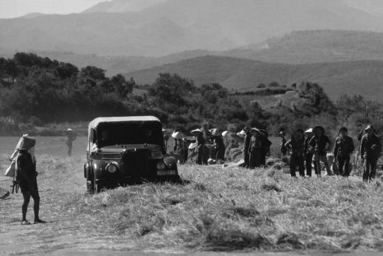 Một chiếc ô tô chạy trên con đường chất đầy những bó lúa vừa gặt. Người nông dân tận dụng điều này thay cho việc đập lúa.