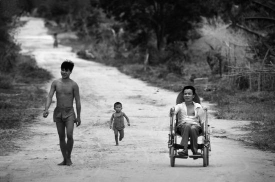 Một cựu chiến bịnh bị chấn thương cột sống do mảnh bom trong thời gian hoạt động trên Đường mòn Hồ Chí Minh ngồi xe lăn trên con đường mòn của làng A Lưới, Huế.