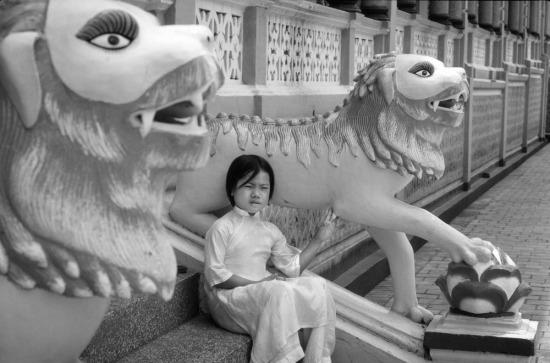 Bé gái mặc áo dài ngồi phía ngoài đền thờ của đạo Cao Đài ở Tây Ninh.