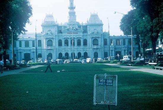"""Tòa Đô chính (UBND Thành phố HCM ngày nay) với tấm bảng yêu cầu """"bỏ giấy vụn vào giỏ này"""" ở bãi cỏ phía trước."""