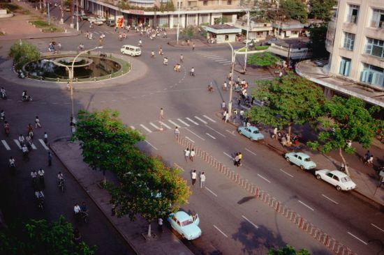 Giao lộ Nguyễn Huệ – Lê Lợi, Sài Gòn năm 1989 nhìn từ khách sạn REX với vòng xoay Cây Liễu nổi tiếng. Vòng xoay này ngày nay không con do đường Nguyễn Huệ đã trở thành phố đi bộ.
