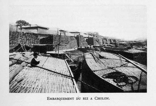 Những chồng bao tải gạo được tập kết tại bến thuyền ở Chợ Lớn.