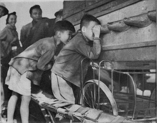Các cậu bé xem phim thùng lưu động trên phố.