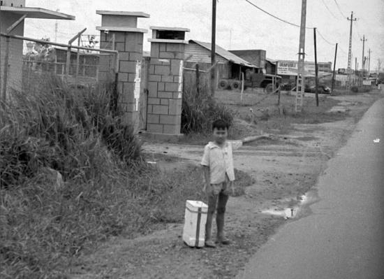 Cậu bé Việt Nam bên một con đường.