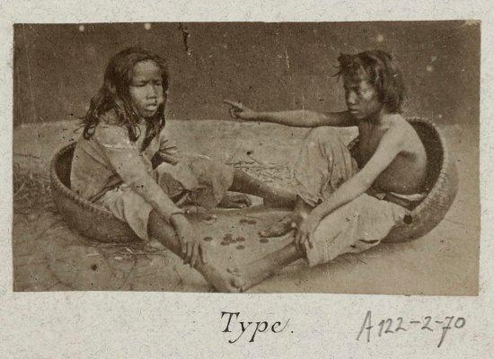 Hai đứa trẻ bốc vác ngồi chơi với những đồng xu.