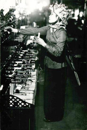 Một nữ công nhân trong Nhà máy dệt tại TP Nam Định. Đây là nhà máy dệt lớn thứ hai của miền Bắc Việt Nam. Phần lớn nhà máy đã được sơ tán về các vùng nông thôn, chỉ còn một vài bộ phận hoạt động tại thành phố. Các công nhân mặc quân phục vừa làm việc vừa đeo súng trường để sẵn sàng chiến đấu.