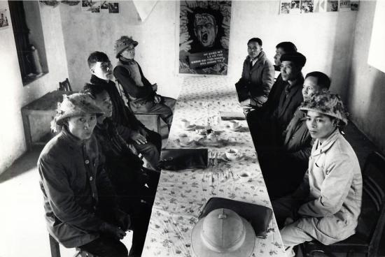 Một bức ảnh tập thể của ban lãnh đạo hợp tác xã nông nghiệp xã Nguyên Xá, huyện Vũ Thư, tỉnh Thái Bình. Trên tường là một tranh cổ động vẽ các ngón tay giận dữ của thế giới chỉ vào mặt Tổng thống đương nhiệm Mỹ Johnson.