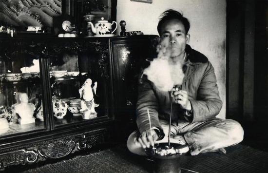 Một xã viên tiên tiến hợp tác xã Nguyên Xá hút thuốc lào tại nhà.