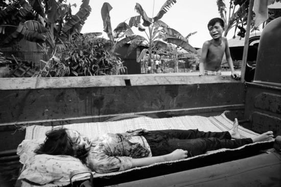 Một cậu bé khóc lóc bên xác chị gái bị thiệt mạng do hỏa lực từ trực thăng Mỹ, được xe tải của sở cứu hỏa Sài Gòn thu gom trên đường phố trong cuộc chiến tại Sài Gòn Tết Mậu Thân 1968,