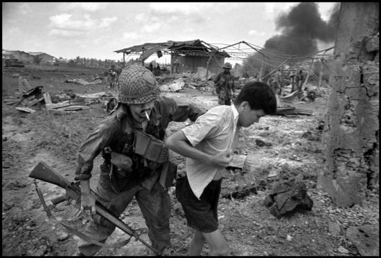 Một thanh niên bị lính Mỹ thuộc Sư đoàn bộ binh số 9 áp giải ở ngoại ô Sài Gòn, 1968.