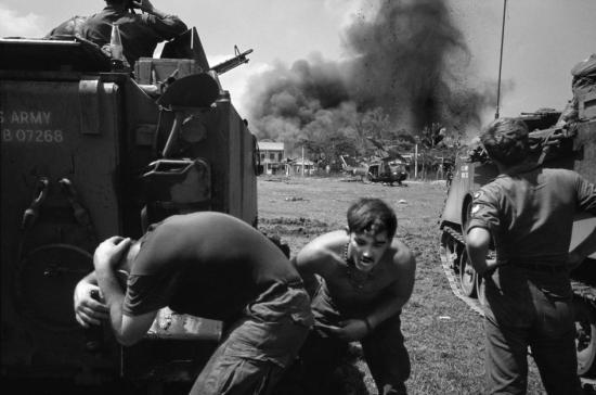 Hai lính Mỹ tỏ ra hốt hoảng trước một vụ nổ xảy ra ở cách đó khá xa. Một người lính khác tỏ ra khá bình thản, 1968.
