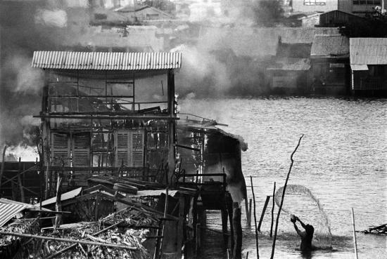 Nỗ lực tuyệt vọng của người dân trong việc cứu ngôi nhà bốc cháy trên bờ sông ở Sài Gòn, 1968.