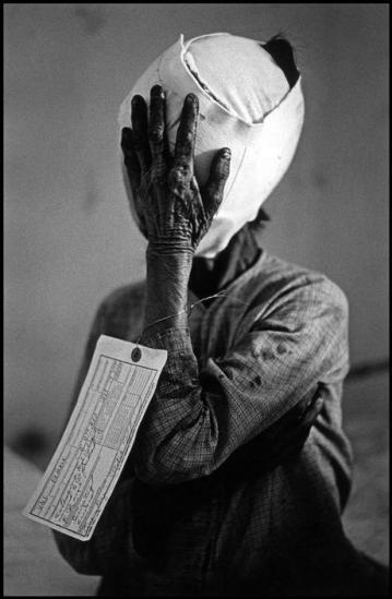 Người phụ nữ bị thương nặng ở mặt này được lính Mỹ gắn thẻ VNC (thường dân Việt Nam). Đây là một điều không bình thường, vì những người bị thương luôn mang thẻ VCS (tình nghi Việt Cộng), và người chết sẽ mang thẻ VCC (xác nhận là Việt Cộng) để không làm tổn hại đến hình ảnh lính Mỹ. Có lẽ tình trạng của bà đã khiến người phụ trách cảm thấy thương hại (Quảng Ngãi, 1967).