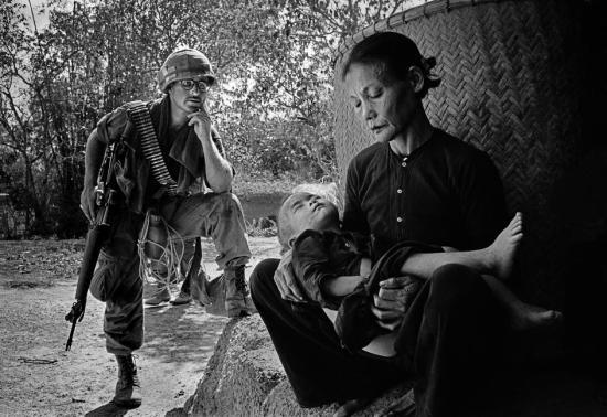 """Lính Mỹ tại một ngôi làng nằm trên hành trình """"tìm - diệt"""" ở Quảng Ngãi, 1967. Trong những chiến dịch như vậy, tất cả những người đàn ông bị phát hiện khi lẩn trốn đều sẽ bị giết. Cũng không hiếm trường hợp lính Mỹ giết cả người già, trẻ em và phụ nữ để làm đẹp những bản báo cáo."""