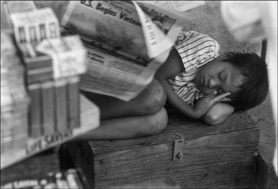 Một đứa trẻ ngủ gục trên đường phố Sài Gòn, 1973.