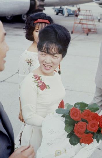 Khi ra sân bay, hai mẹ con mặc áo dài trắng thêu hoa. Ảnh: John Leongard.