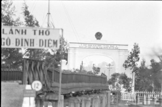 """Đối diện với cổng chào có phần """"mong manh"""" của Sài Gòn là cánh cổng xây bằng bê tông bề thế và vững chắc của Việt nam Dân chủ cộng hòa."""