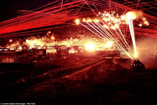 """Trong ảnh, các khẩu pháo Bofors cỡ nòng 40mm và súng máy từ xe M42 bắn đốt cháy quả núi, còn các tia màu đỏ chằng chịt là của súng máy M60 trên các tháp canh của doanh trại quân Mỹ. Trong đêm kinh hoàng này, do không biết chính xác nơi ẩn nấp của người lính bắn tỉa Việt Nam, quân Mỹ đã """"hỏa thiêu"""" toàn bộ vùng đồi núi."""